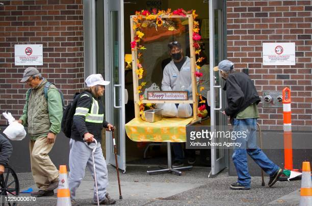 Oct. 10, 2020 -- A volunteer wearing a face mask serves meals during the Thanksgiving dinner event in Vancouver, British Columbia, Canada, on Oct....