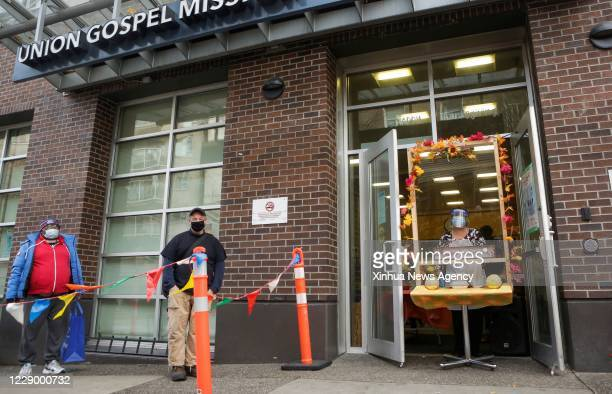 Oct. 10, 2020 -- People wait with physical distancing to pick up their meals during the Thanksgiving dinner event in Vancouver, British Columbia,...