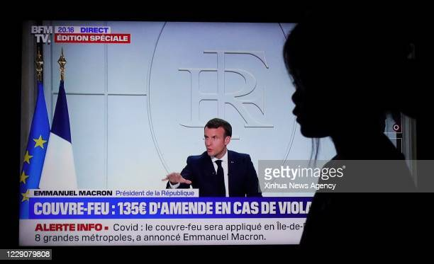 Oct. 14, 2020 -- A spectator watches a screen displaying French President Emmanuel Macron as he receives a televised interview concerning the...