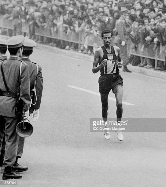 Abebe Bikila of Ethiopia runs through the streets of Tokyo, on his way to winning the marathon at the 1964 Olympic Games in Tokyo. In 1960 in Rome, barely known outside his country, he ran barefoot to become the first black African to winan Olympic title. Four years later, he wore shoes and won by an even greater margin, just five weeks after having his appendix removed and losing eleven days training in his final preparation. Sadly he was badly injured in a car crash five years laterand died prematurely at the age of 41. Under a bursary scheme provided by the IOC, his two children completed their education at Loughborough College in Britain. Mandatory Credit: IOC/Allsport