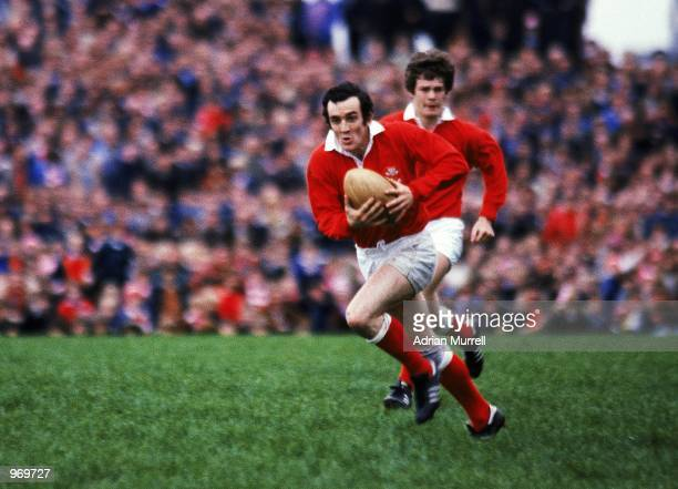 Phil Bennett of Llanelli runs with the ball during the Rugby Union International Friendly match against New Zealand to commerate the Welsh Centenary...