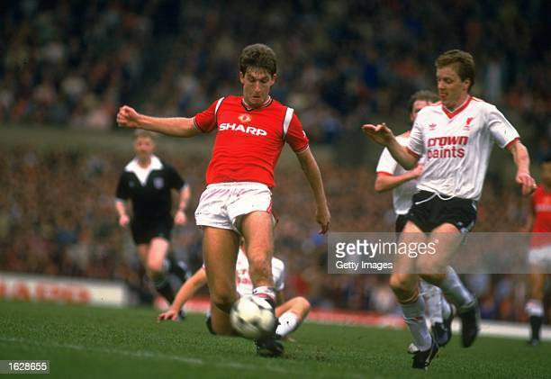 Steve Nicholl of Liverpool comes in to tackle Norman Whiteside of Manchester United during a Canon League Division One match at Old Trafford in...