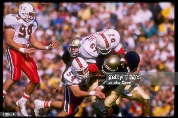 Defensive tackle Russell Maryland and defensive end Bill Hawkins of the Miami Hurricanes hit quarterback Tony Rice of the Notre Dame Fighting Irish...