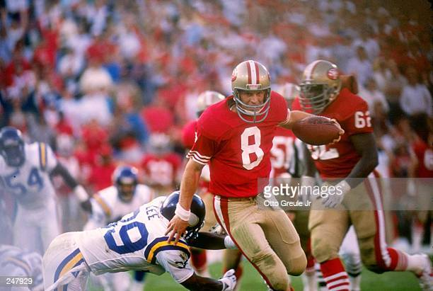 Quarterback Steve Young of the San Francisco 49ers tries to break a tackle during a game against the Minnesota Vikings at Candlestick Park in San...