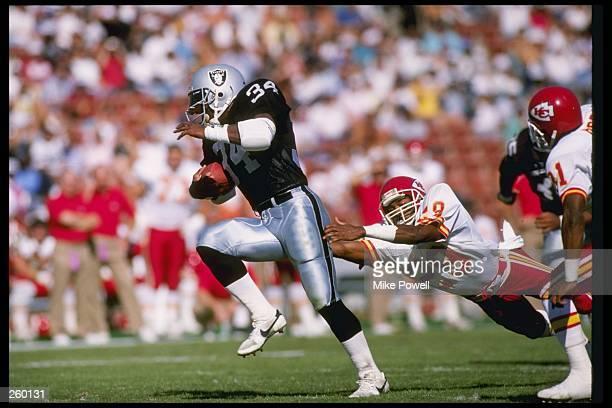 Running back Bo Jackson of the Los Angeles Raiders moves the ball during a game against the Kansas City Chiefs at the Los Angeles Memorial Coliseum...