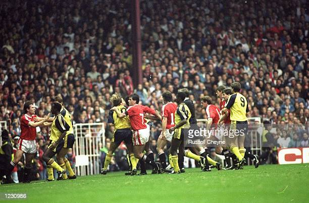Manchester United and Arsenal players fight on the pitch during the Barclays League Division One match at Old Trafford in Manchester, England....