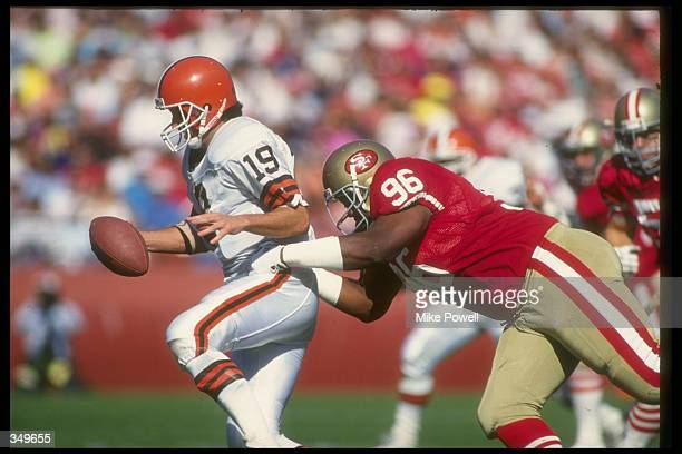 Quarterback Bernie Kosar of the Cleveland Browns attempts to avoid the tackle of San Francisco 49ers defensive lineman Dennis Brown during a game at...
