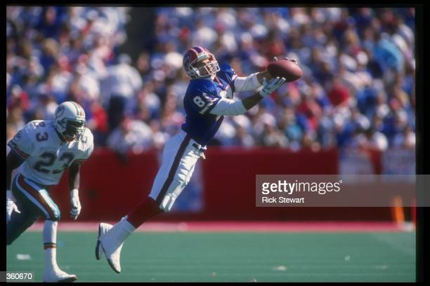 Wide receiver Brad Lamb of the Buffalo Bills catches the ball as a Miami Dolphins player looks on during a game at Rich Stadium in Orchard Park, New...