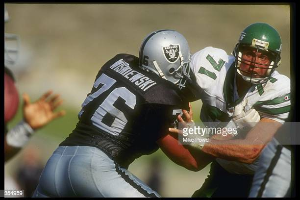 Defensive lineman Bill Pickel of the New York Jets and Los Angeles Raiders offensive lineman Steve Wisniewski tangle up during a game at the Coliseum...