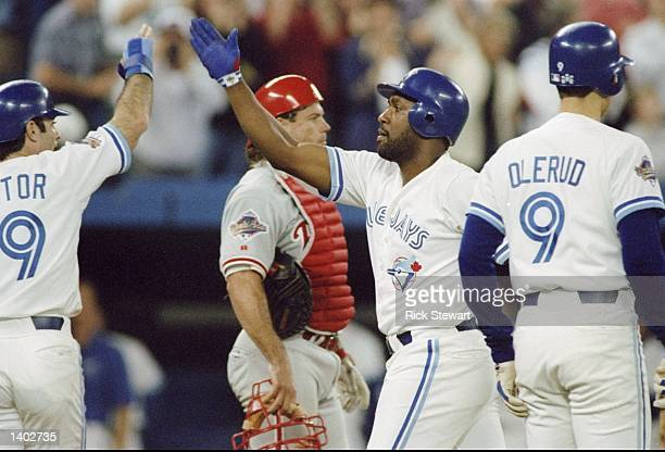 Firrst baseman Joe Carter of the Toronto Blue Jays high fives his teammates during the World Series against the Philadelphia Phillies at the Toronto...