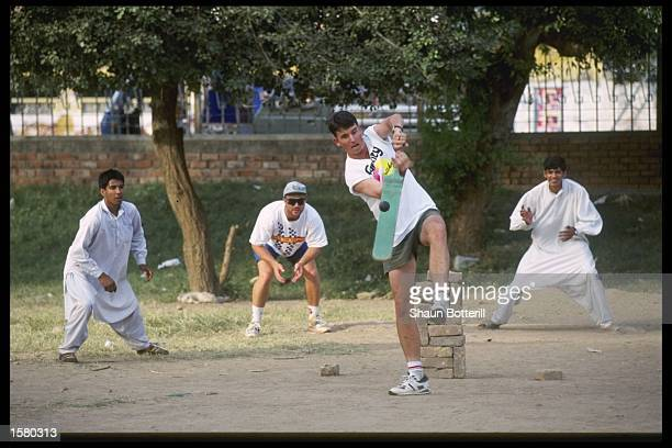 Damien Fleming of Australia plays street cricket with the locals during Australia's tour to Pakistan Teammate Michael Slater fields at first slip...