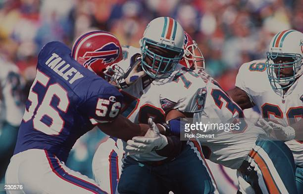 Richmond Webb of the Miami Dolphins holds back Talley of the Buffalo Bills during the Dolphins 21-11 loss to the Bills at Rich Stadium in Orchard...