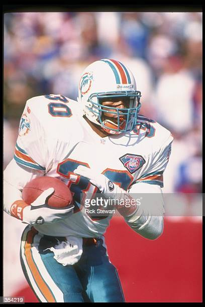 Running back Bernie Parmalee of the Miami Dolphins runs with the ball during a game against the Buffalo Bills at Rich Stadium in Orchard Park, New...