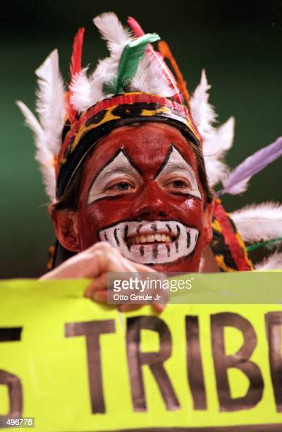 Fan of the Cleveland Indians paints his face and wears an Indain headdress in support during a game against the Atlanta Braves at the Jacobs Field in...