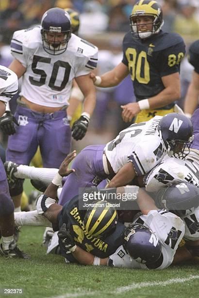 Defensive back Chris Martin of the Northwestern Wildcats tackles runningback Tshimanga Biakabatuka of the Michigan Wolverines at Michigan Stadium in...