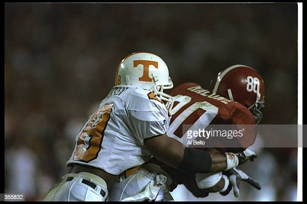 Defensive back Raymond Austin of the Tennessee Volunteers tackles Alabama Crimson Tide player Todd Malone during a game at Legion Field in Tuscaloosa...