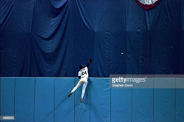Ken Griffey Jr. #24 of the Seattle Mariners reaches for Carlos Baerga's home run ball at the wall during game six of the ALCS against the Cleveland...