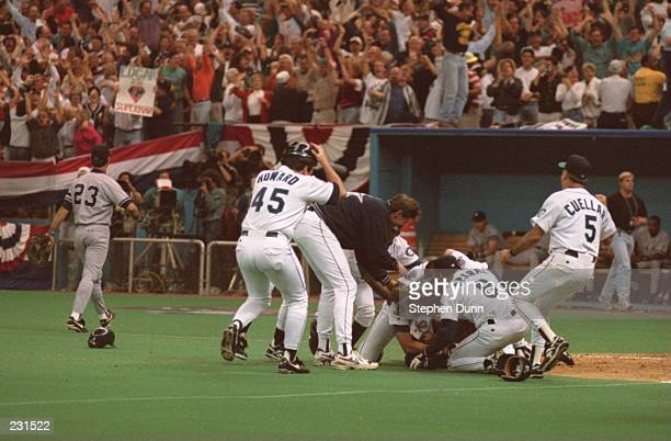 NEW YORK FIRST BASEMAN DON MATTINGLY WALKS OFF THE FIELD AS SEATTLE CELEBRATES AT HOME PLATE IMMEDIATELY FOLLOWING THE MARINERS'' 65 VICTORY