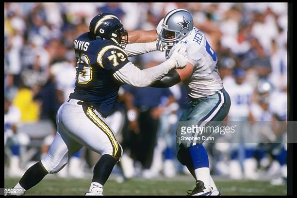 Offensive lineman Isaac Davis of the San Diego Chargers blocks Dallas Cowboys defensive lineman Chad Hennings during a game at Jack Murphy Stadium in...