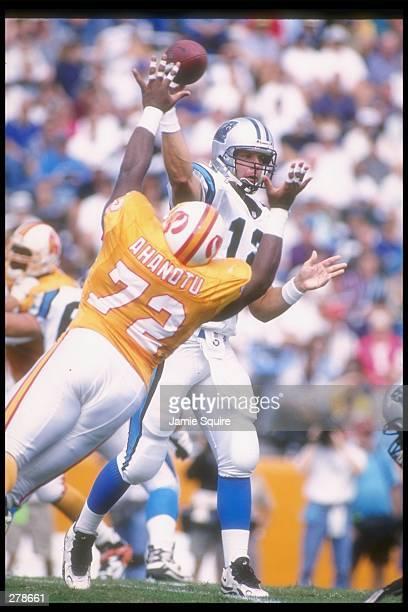 Quarterback Kerry Collins of the Carolina Panthers passes the ball as Tampa Bay Buccaneers defensive lineman Chidi Ahanotu atempts to block him...