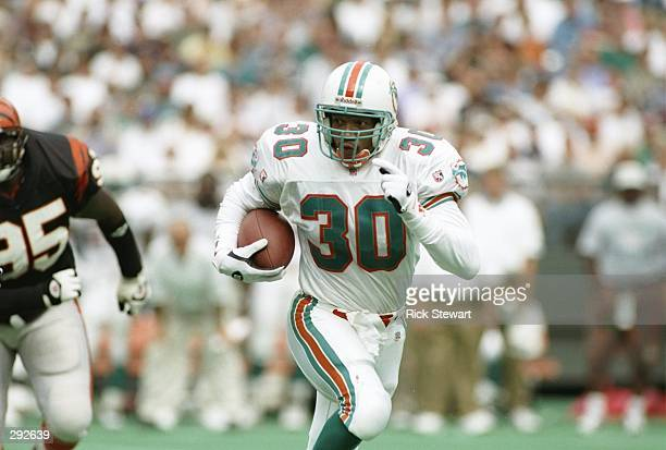 Runningback Bernie Parmales of the Miami Dolphins runs down the field as defensive linemen Keith Rucker of the Cincinnati Bengals chases after him...