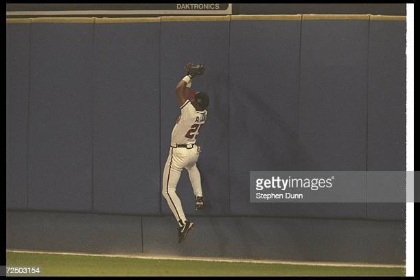 Andruw Jones of the Atlanta Braves catches a ball during Game Three of the World Series against the New York Yankees at Fulton County Stadium in...