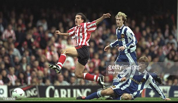 Eyal Berkovic of Southampton leaps over the tackle of David Beckham of Manchester United whilst Jori Cruyff looks on during the FA Carling Premier...
