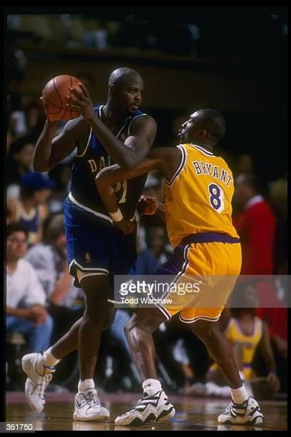 Forward George McCloud of the Dallas Mavericks moves the ball as Los Angeles Lakers guard Kobe Bryant covers him during a game at Selland Arena in...