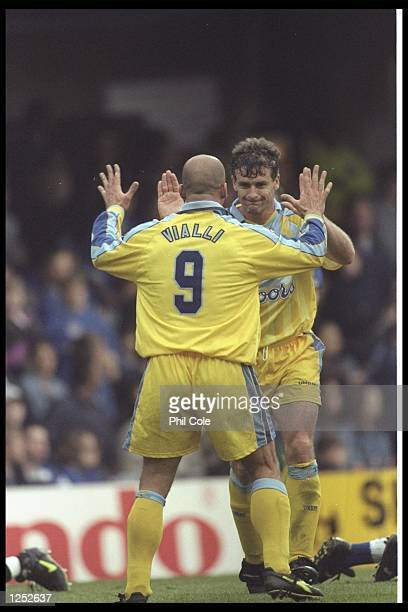 Gianluca Vialli of Chelsea congratulates teammate Mark Hughes after scoring Chelsea's third goal during the FA Carling Premier league match between...