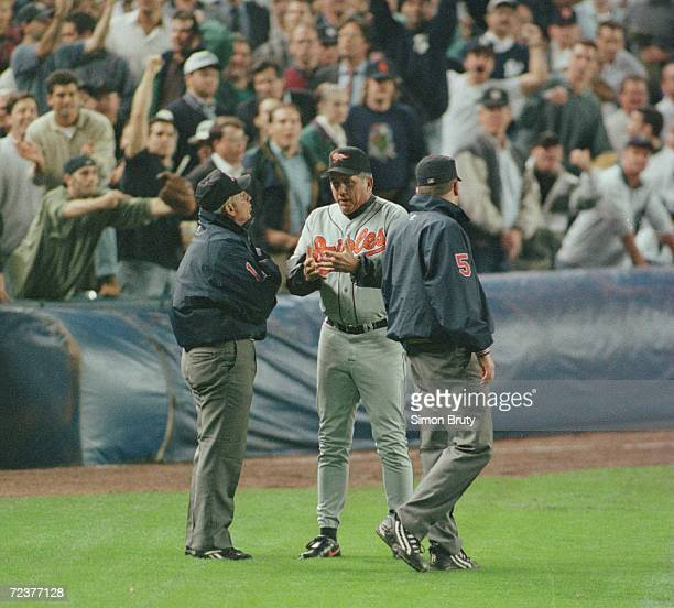 Manager Davey Johnson of the Baltimore Orioles argues with umpire Rich Garcia and Dale Scott over a fan interferance when Tony Tarasco tried to make...
