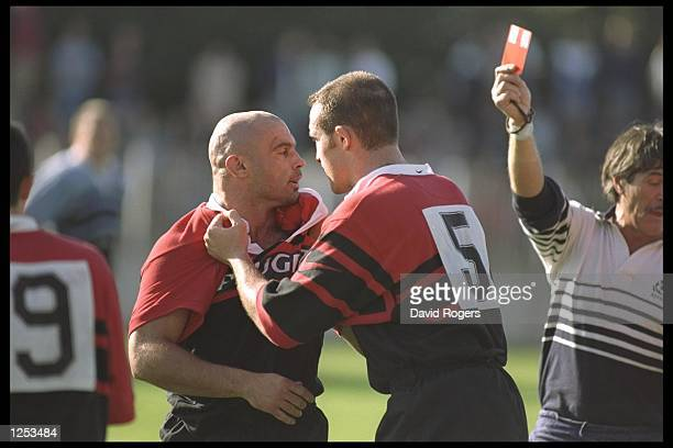 Partick Soula of Tolouse recieves a red card as F Belot restrains him during the Heineken European Cup match between Tolouse and Cardiff in France...