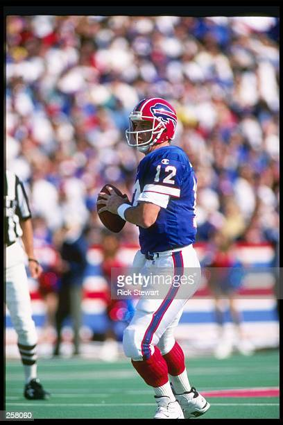 Quarterback Jim Kelly of the Buffalo Bills looks to pass the ball during a game against the Miami Dolphins at Rich Stadium in Orchard Park, New York....