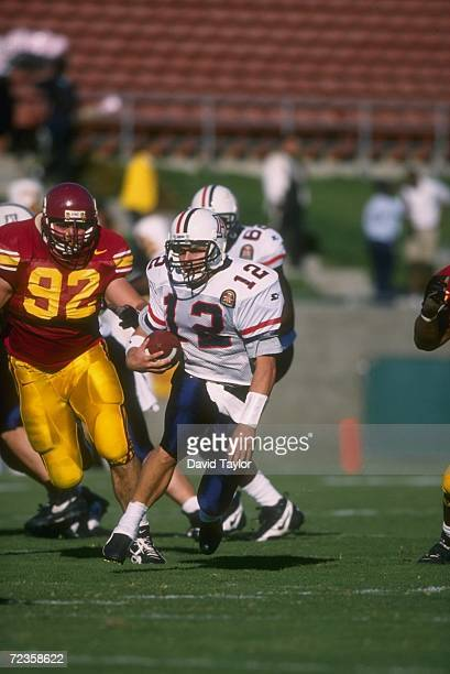 Quarterback Keith Smith of the Arizona Wildcats looks upfield for pursuing defenders from the USC Trojans as he runs with the football during a carry...