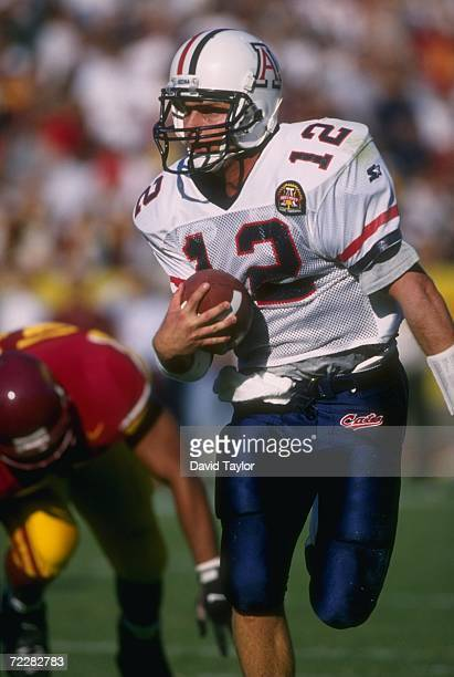 Quarterback Keith Smith of the Arizona Wildcats looks up field for pursuing tacklers from the USC Trojans as he bursts through a hole in the...
