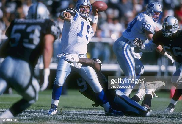 Quarterback Scott Mitchell of the Detroit Lions looks down field at an open receiver as he sets to through football despite the pressure applied by a...