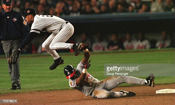 Shortstop Derek Jeter of the New York Yankees leaps over Andruw Jones of the Atlanta Braves after forcing him out to turn a double play in the second...