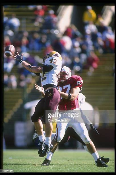 Tight end Greg Clark of the Stanford Cardinal attempts to catch the ball as Arizona State Sun Devils linebacker Pat Tillman covers him during a game...