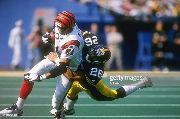 Wide receiver Carl Pickens of the Cincinnati Bengals uses his left arm to brace himself as he is hit from behind by defensive back Rod Woodson of the...