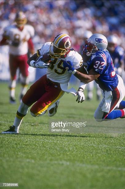 Wide receiver Henry Ellard of the Washington Redskins hangs onto the football as he attempts to run through the diving grasp of defensive back Willie...