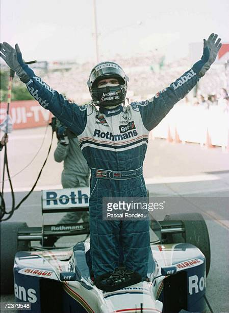 Williams driver Damon Hill of Great Britain gets out of his car and waves as he celebrates after winning the Japanese Formula One Grand Prix and the...