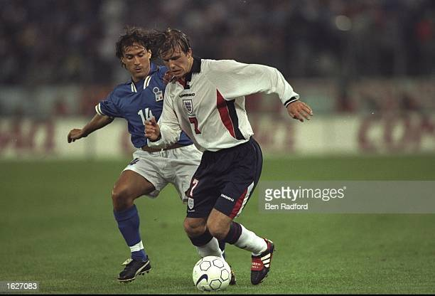David Beckham of England is chased by Antonio Benarrivo of Italy during the World Cup Qualifier at the Olympic Stadium in Rome Italy The game ended...