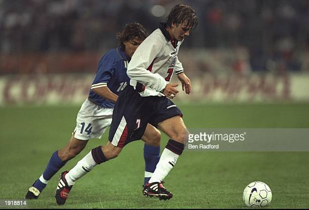 David Beckham of England is tracked by Antonio Benarrivo of Italy during the World Cup Qualifier at the Olympic Stadium in Rome Italy The game ended...