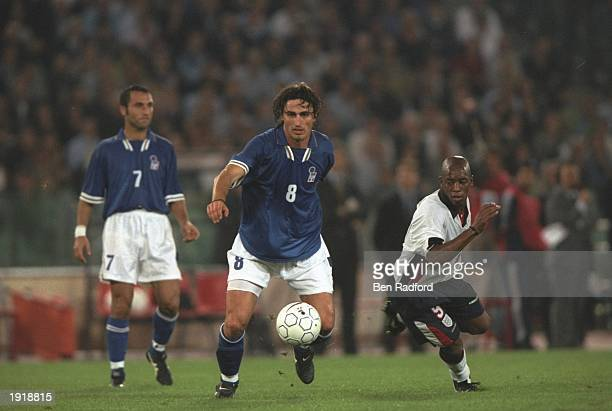 Dino Baggio of Italy and Ian Wright of England compete for the ball whilst Angelo di Livio of Italy watches on during the World Cup Qualifier at the...