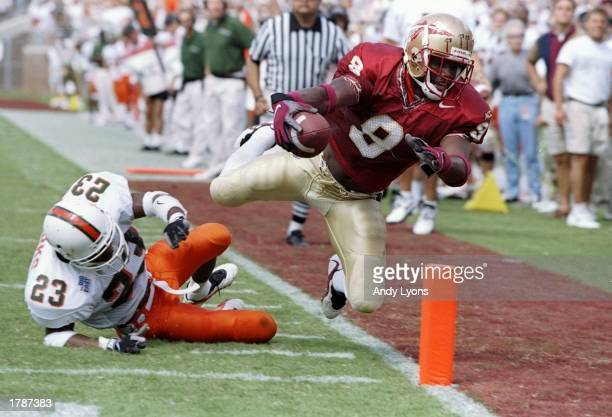 Flanker Peter Warrick of the Florida State Seminoles makes a touchdown as cornerback Duane Starks of the Miami Hurricanes misses the tackle during a...