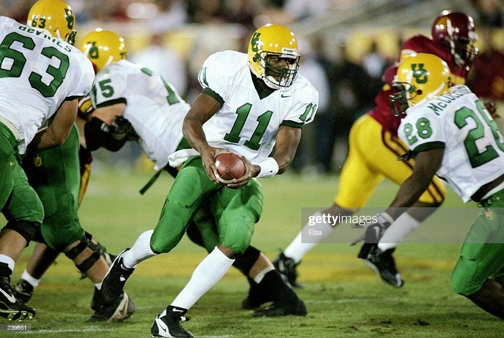 Quarterback Akili Smith of the Oregon Ducks scrambles with the ball as tailback Saladin McCullough (right) goes into action during a game against the USC Trojans at the Los Angeles Memorial Coliseum in Los Angeles, California. USC won the