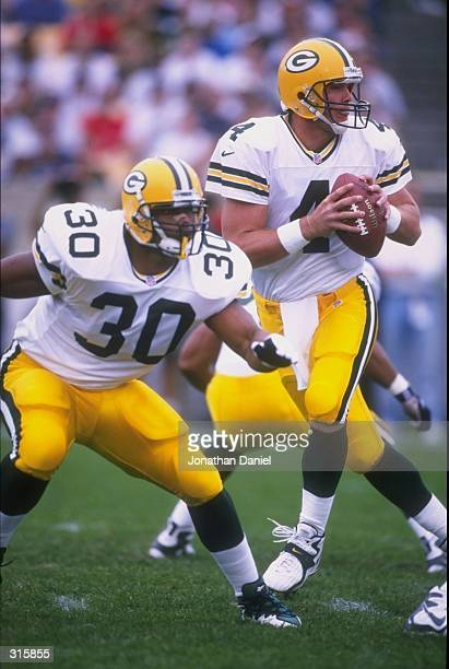 Quarterback Brett Favre of the Green Bay Packers looks for an open receiver as William Henderson blocks for Favre during a game against the Chicago...