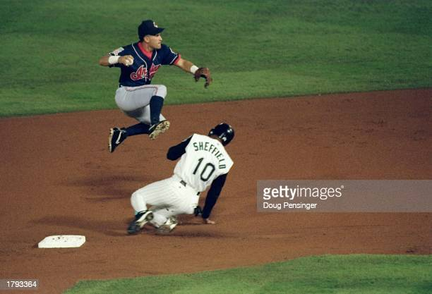 Runner Gary Sheffield of the Florida Marlins slides under Shortstop Omar Vizquel of the Cleveland Indians in an attempt at a double play during Game...