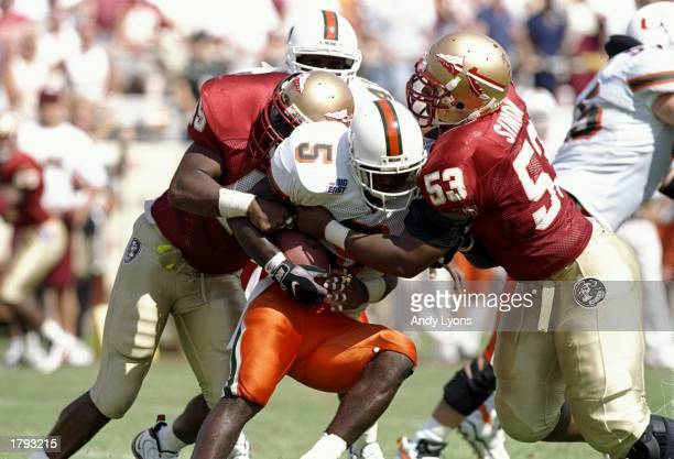 Running back Edgerrin James of the Miami Hurricanes gets tackled during a game against the Florida State Seminoles at Doak S Campbell Stadium in...
