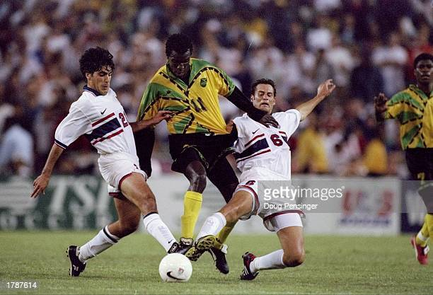 Theodore Whitmore of Jamaica tries to get the ball away from Claudio Reyna and John Harkes of the United States during a World Cup qualifier match at...