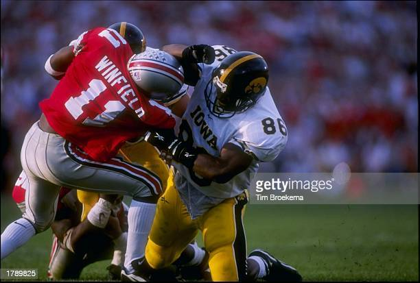 Tight end Austin Wheatley of the Iowa Hawkeyes tangles with cornerback Antoine Winfield of the Ohio State Buckeyes during a game at Ohio Stadium in...